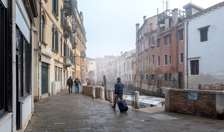 Tourist with suitcase in an alley in Venice Editorial