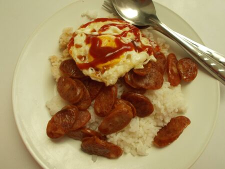 cooked rice: Fried Chinese sausage and fried egg together with cooked rice.