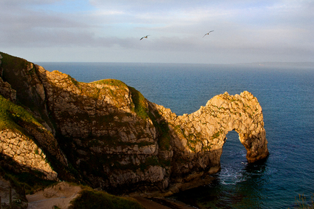 Sun rising at famous Durdle Door, iconic rock formation of the English coastline