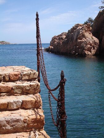 steps and rusty chain fence with the mediteranean in the background Stock Photo