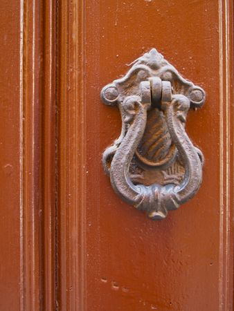 Old door hands shaped Knocker on an old wooden door