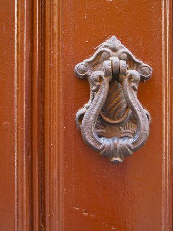 Old door hands shaped Knocker on an old wooden door
