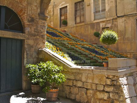 Old town Girona steps with flowers and stone walls