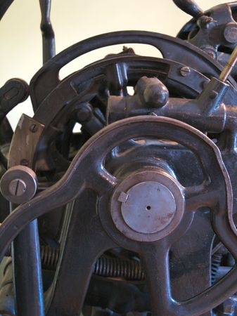 Old printing press with cogs, bars, wheels and levers