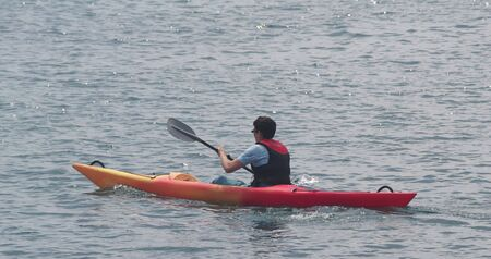 paddler with sea kayak on the sea int he harbour