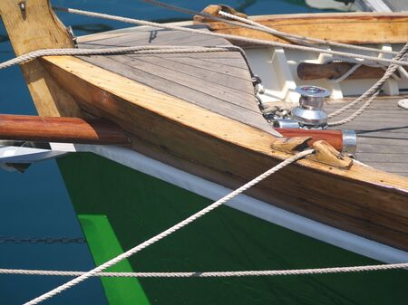 Bow and deck of wooden boat with ropes and water