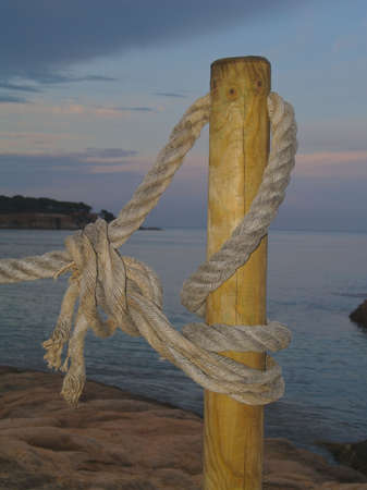 Rope tied to a wooden post with St Pol bay in the background