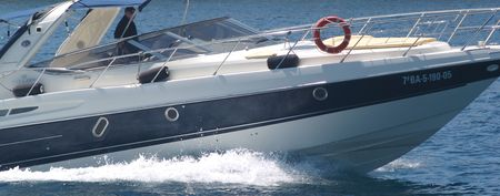 Powerful motor boat coming into mediteranean harbour Stock Photo
