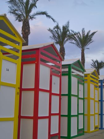 colourful bathing huts at St Pol beach with palm Trees Stock Photo