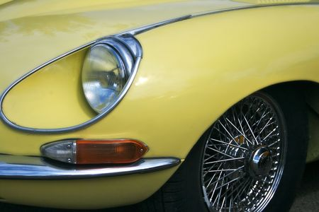 Yellow wing of an E Type and the chrome wire wheels.