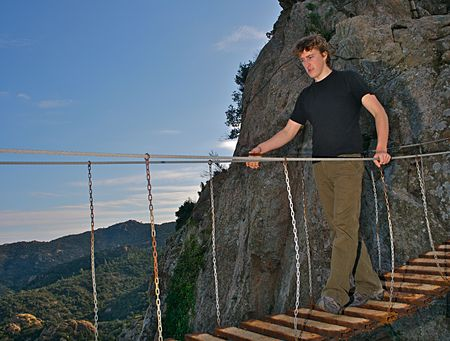 wire and metal hanging bridge over deep ravine