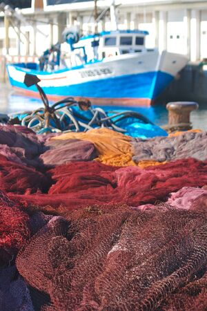 Fishing nets in the foregroung with a fishing boat tied up at the harbour