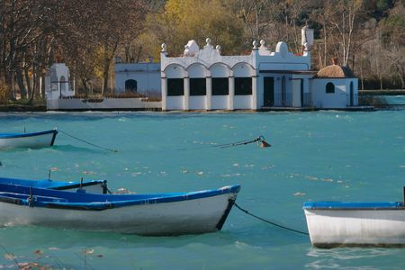 Brilliant turquoise coloured lake with a boat house beside the lake and rowing boats bobbing Stock Photo