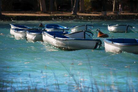 encrespado: Botes a remo en un lago agitado por el viento hasta que las olas  Foto de archivo