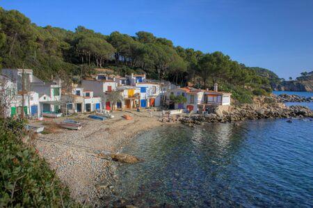 Stoney beach with colourful beach houses at Platja Castel Baix Emporda, Costa Brava