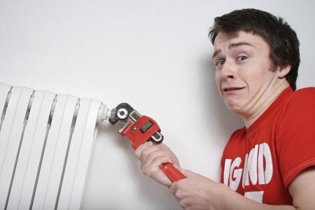 workingman: Plomero muchacho con llave inglesa a punto de poner cargas de las inundaciones de agua en el suelo