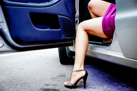 Young sexy woman in purple dress get out of the car Archivio Fotografico