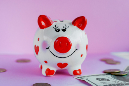 Savings concept. Funny piggy bank and on pink background Stock Photo