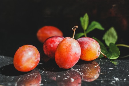 fresh plum on a black background with green leaves