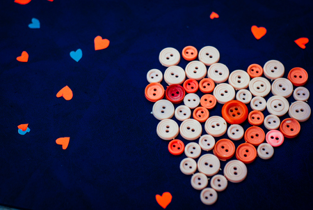 Sewing buttons in the shape of a heart on a retro blue background