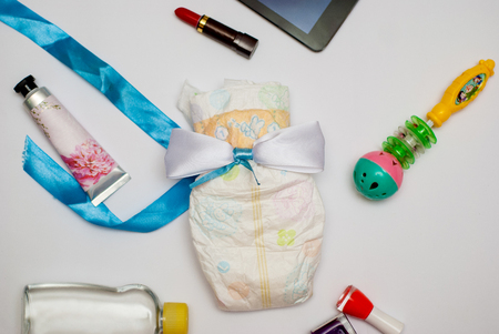 Contents of a woman's bag on white background. Contents include: tablet, lipstick, hand cream, nail polish, baby oil, toy and a diaper.