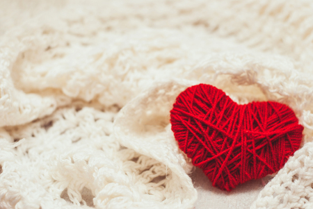 red knitted heart symbol on white background Archivio Fotografico