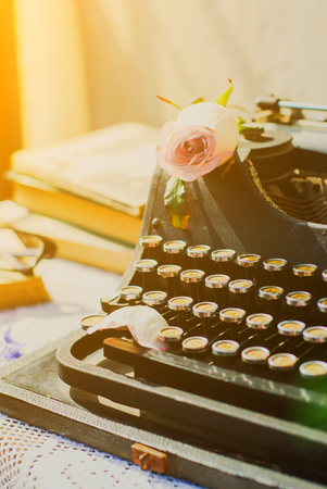 Vintage typewriter with pink rose , old books on table. Stock Photo