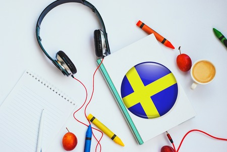 the book with swedish flag and headphones. concept of swedish learning through audio courses