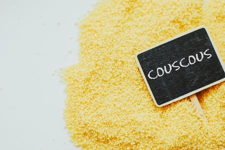 Raw cous cous with chalkboard with word couscous. copy space