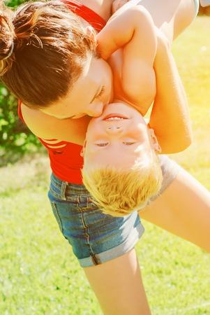 Young brunette mother lifting her son in park having fun enjoying motherhood. Stock Photo