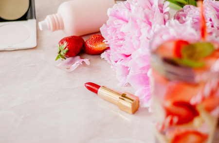 Beauty flat lay with a cosmetics, perfum, detox water with strawberry and peonies on a marble background. Top view