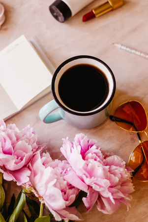Beauty flat lay with a diary, cup of coffee, accessories and peonies on a marble background. Top view