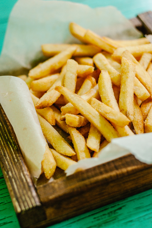 French fries on basket on wooden background Stock Photo