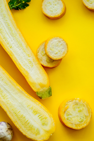 Creative layout of solid and sliced yellow zucchini on yellow background with space for text. Stock Photo