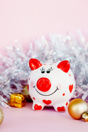 Piggy bank over pink background with christmas decoration copy space. Year of pig 2019.