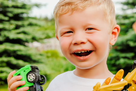 Portrait of cute happy little blond boy holding plane and car toys. Adorable child walking in park on sunny day. Summertime Outdoors. Childhood, lifestyle concept