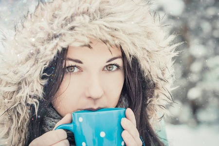 Woman with big mug of hot drink during cold day.