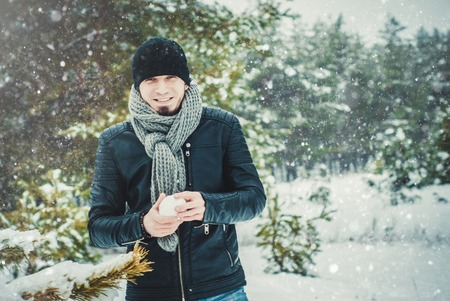 A young man throwing a snowball in the forest Stok Fotoğraf