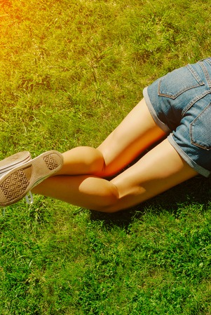 Young woman lying in the grass in a sunny summer day. Legs. 写真素材