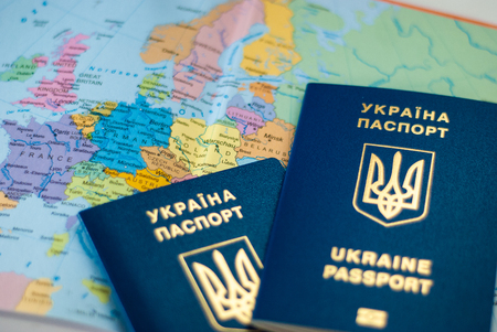 Ukrainian international biometric passport on a map background. immigration kit for earnings or vacations. Stock Photo