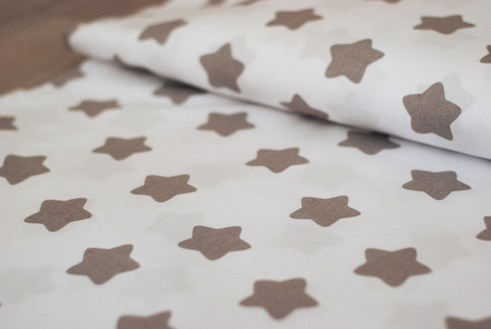 The texture of cotton fabric. Fabric with a pattern of stars creates a textural background. Natural cotton fabric for sewing. 스톡 콘텐츠
