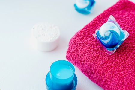 Washing detergent capsule pods and pink towel isolated on white background. 스톡 콘텐츠
