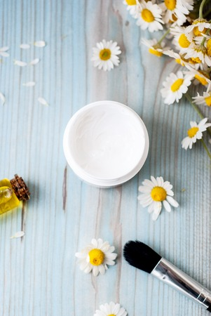 Holistic homemade herbal cosmetics with camomile, essential oils, bowls, facial cream, top view white wooden table. 스톡 콘텐츠