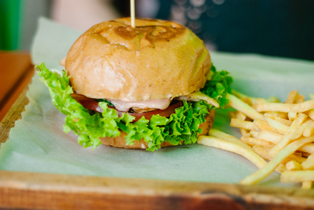 chicken burger with french fries on a wooden table
