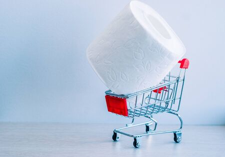 a roll of white toilet paper in a shopping cart as a symbol of consumer panic about coronavirus