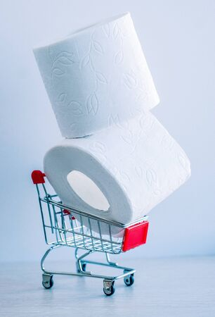 a roll of toilet paper in a shopping cart as a symbol of consumer panic about coronavirus 스톡 콘텐츠