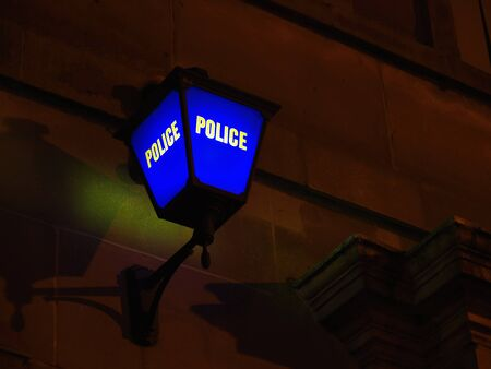 A blue lamp outside a police station at night Stock Photo