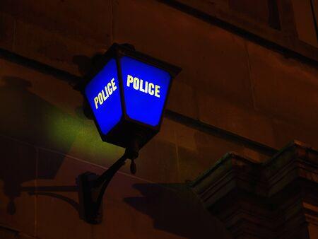 Eine blaue Lampe außerhalb einer Polizeistation in der Nacht