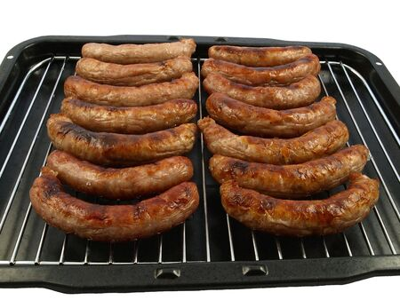 A grill pan of cooked pork sausages - isolated on white