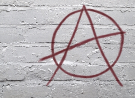 dissent: Urban graffiti red anarchy symbol on whitewashed brickwork